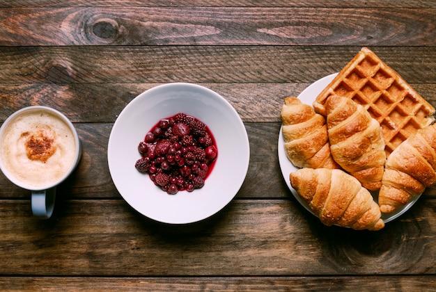 Panadería en un plato cerca de una taza de bebida y mermelada Foto gratis