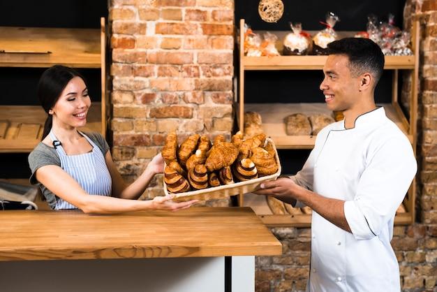 Panadero femenino y masculino que sostiene la cesta de croissant cocido al horno en la pastelería Foto gratis
