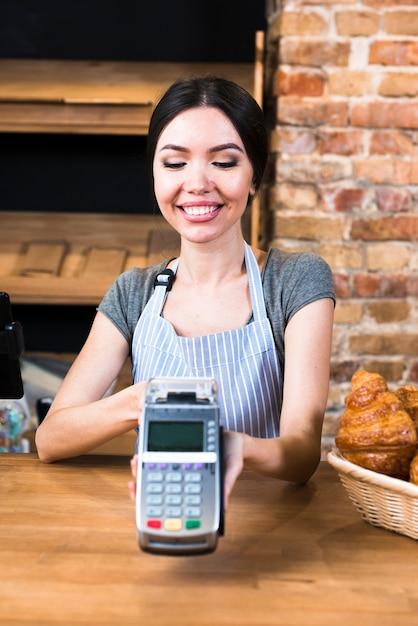 Panadero de sexo femenino feliz que sostiene el terminal del banco en tienda de la panadería Foto gratis