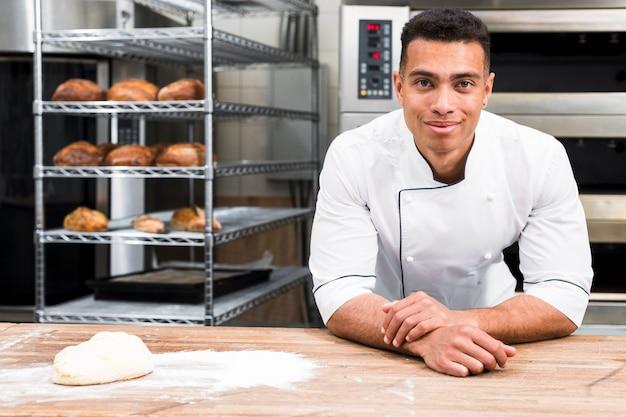 Panadero de sexo masculino de pie detrás de la mesa con masa en la panadería Foto gratis