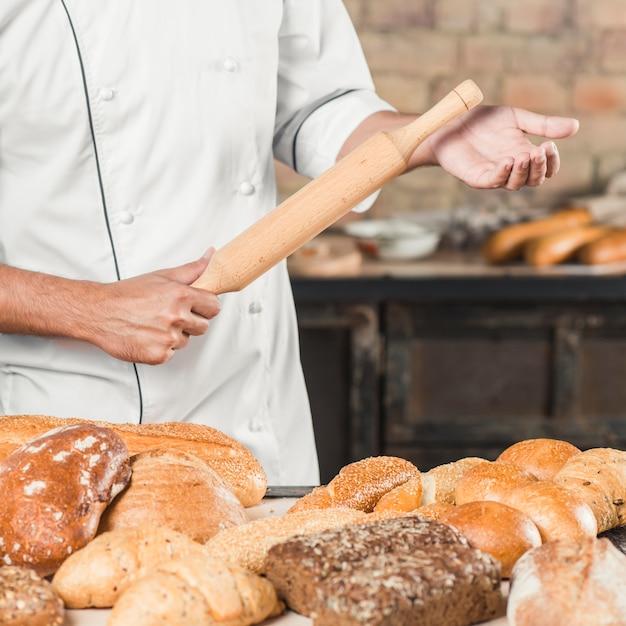 Panadero de sexo masculino que sostiene el rodillo de madera con la variedad de panes en la tabla Foto gratis