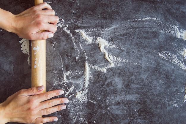 Panadero de la vista superior que prepara el tablero con la harina Foto gratis