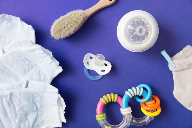 Pañal; cepillo; chupete; botella de leche; calcetín y sonajero sobre fondo azul Foto Premium