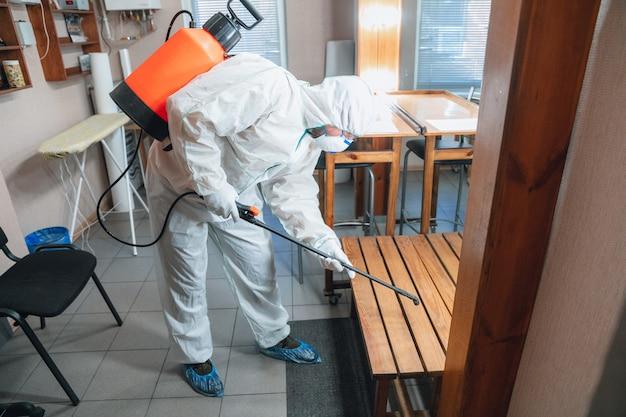 Pandemia de coronavirus. desinfectante en un traje protector y mascarilla rocía desinfectantes en la casa u oficina Foto gratis