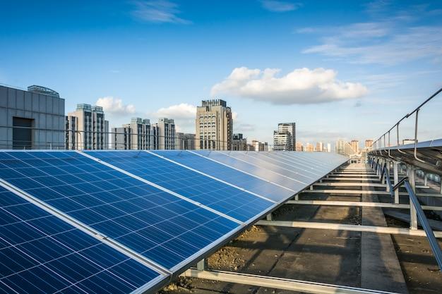 Paneles fotovoltaicos en frente de la ciudad Foto Premium