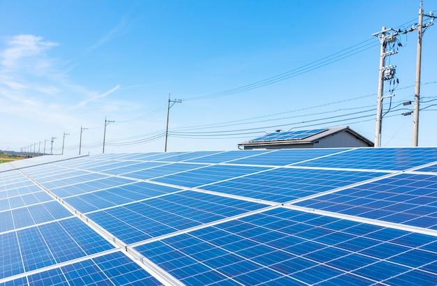 Paneles solares (células solares) en una granja solar con cielo azul y luz solar Foto Premium