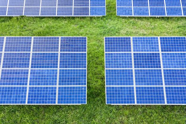Paneles solares que producen energía limpia renovable en la hierba verde. Foto Premium