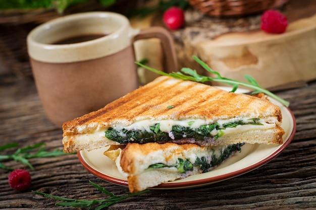 Panini sandwich con queso y hojas de mostaza. cafe mañanero. desayuno del pueblo Foto gratis