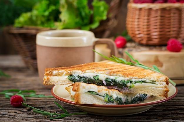 Panini sandwich con queso y hojas de mostaza. cafe mañanero. desayuno del pueblo Foto Premium