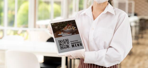 Panorama de cerca la camarera con mascarilla y protector facial sostenga la tableta digital con código qr para que el cliente escanee el menú sin contacto en línea concepto sin contacto y de tecnología para el nuevo restaurante normal Foto Premium