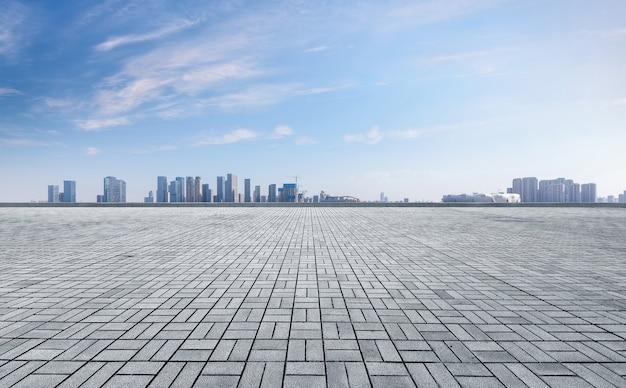 Panorámica del horizonte y edificios con piso cuadrado de concreto vacío. Foto Premium