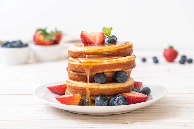 Panqueques con arándanos frescos, fresas frescas y miel. Foto Premium