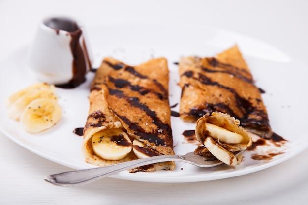 Panqueques con cobertura de plátano y chocolate. Foto Premium
