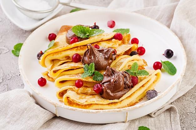 Panqueques con fresas y chocolate decorado con hojas de menta. desayuno sabroso Foto gratis