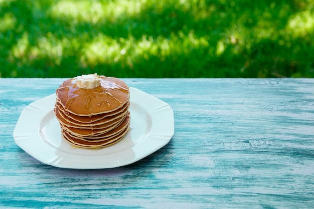 Panqueques con mantequilla y miel en plato blanco en jardín de madera azul o en la naturaleza. pila de panqueques de oro o torta de panqueques, primer de oro. Foto Premium