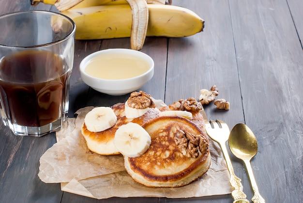 Panqueques con plátano, nueces, miel y taza de café oscuro Foto Premium
