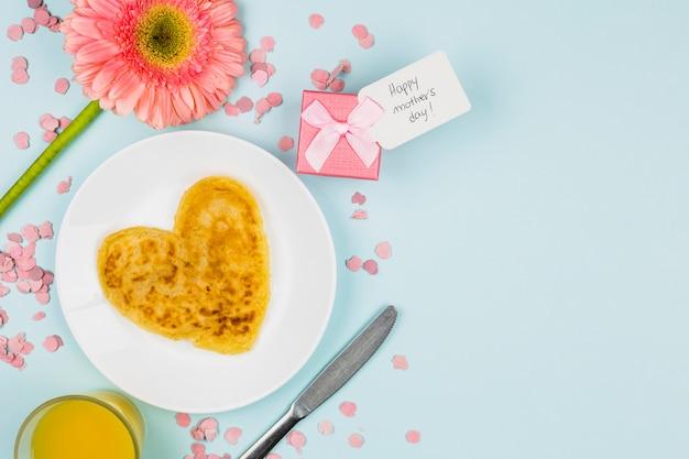 Panqueques en un plato cerca de la flor, vidrio y presente con etiqueta Foto gratis