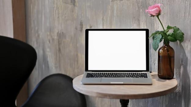Pantalla en blanco del portátil con rosas en un jarrón sobre la mesa de madera. Foto Premium