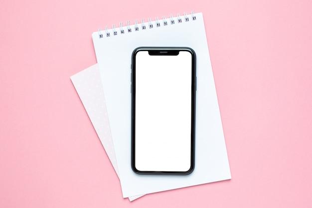 Pantalla en blanco del teléfono móvil y cuaderno del negocio en rosa. escritorio de trabajo de la mujer. Foto Premium