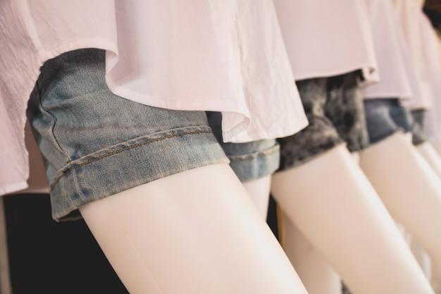 Pantalones cortos modernos rasgados de los tejanos en el modelo del maniquí. Foto Premium