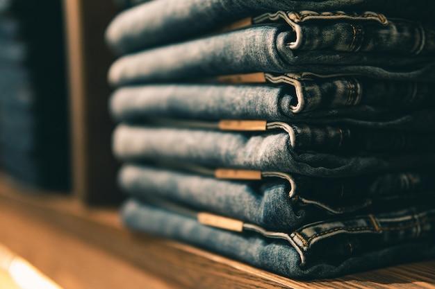 Pantalones vaqueros apilados con múltiples tallas de cintura en estantes o armarios y enfoque selectivo. Foto Premium