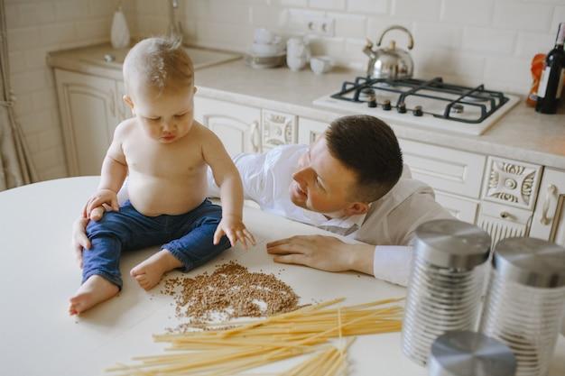 Papá mira a su pequeño hijo sentado en la mesa Foto gratis