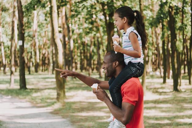 Papá le muestra el camino a la niña que está sentada en su cuello. Foto Premium