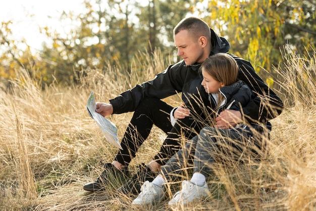 Papá y niña leyendo un mapa en la naturaleza Foto gratis
