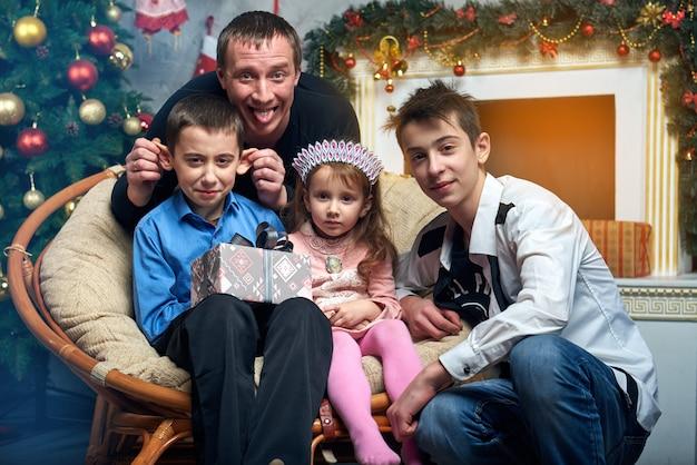 Papá con tres hijos cerca del árbol junto a la chimenea con regalos. Foto Premium