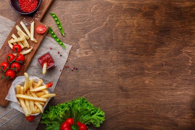 Papas fritas en una cuadrícula con salsa de tomate, ensalada y tomates cherry en una mesa de madera marrón Foto Premium
