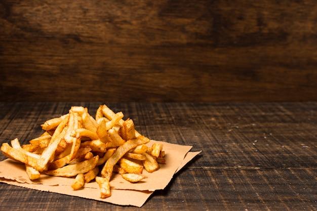 Papas fritas en la mesa de madera Foto gratis