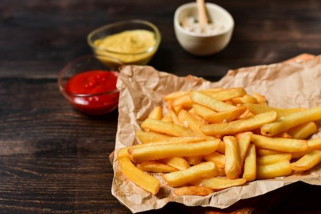 Papas fritas con salsa de tomate, mostaza y sal. almuerzo de comida rápida en una mesa de madera. menú de almuerzo de negocios, entrega de comida rápida. Foto Premium