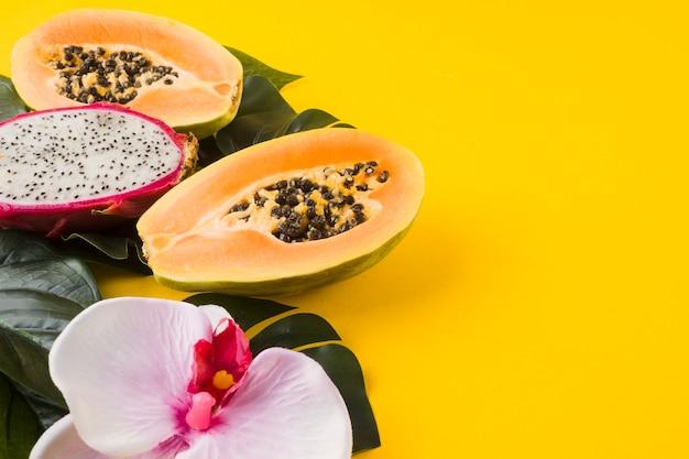 Papaya y fruta de dragón a la mitad frescas con flor de orquídea y hojas sobre fondo amarillo Foto gratis