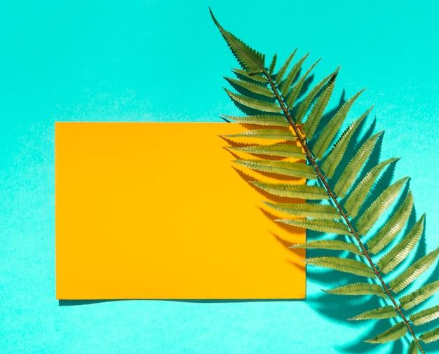 Papel amarillo y hoja de árbol. Foto gratis