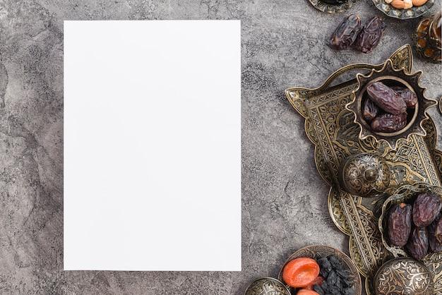 Papel blanco en blanco de ramadan kareem con fechas premium y frutas secas en el fondo Foto gratis