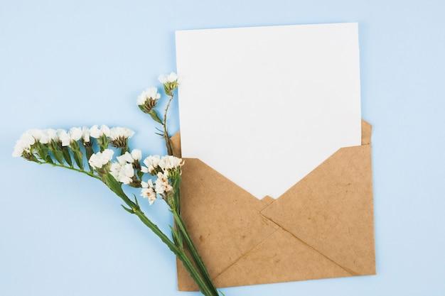 Papel en blanco blanco en el sobre marrón con flores blancas sobre fondo azul Foto gratis
