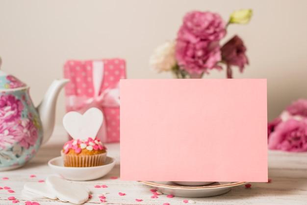 Papel cerca de delicioso pastel, caja de regalo y tetera. Foto gratis