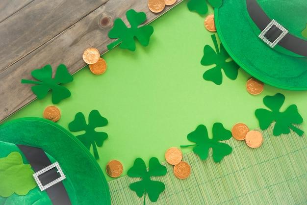 Papel cerca de monedas, tréboles decorativos y sombrero de san patricio. Foto gratis