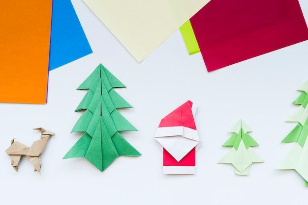 Papel colorido y árbol de navidad hecho a mano; reno; papá noel origami de papel aislado sobre fondo blanco Foto gratis