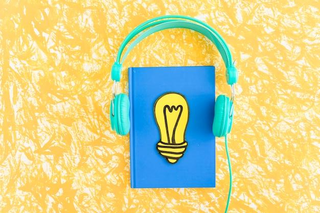 Papel cortado bombilla de luz amarilla en el cuaderno cerrado con auriculares en el fondo con textura Foto Premium