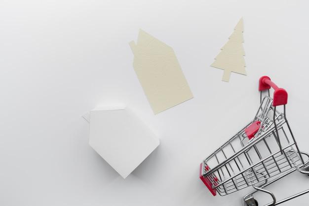 El papel cortó la casa y el árbol de navidad con el modelo miniatura de la casa y el carro de compras aislados en el fondo blanco Foto gratis