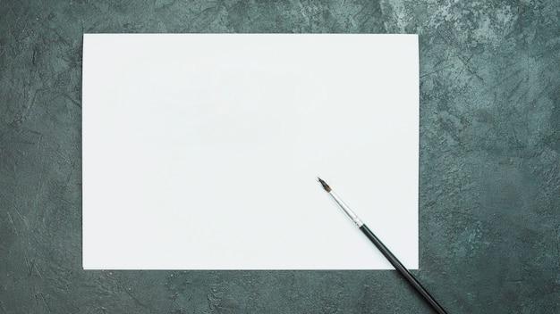 Papel de dibujo blanco en blanco con pincel sobre negro pizarra roca texturada Foto gratis