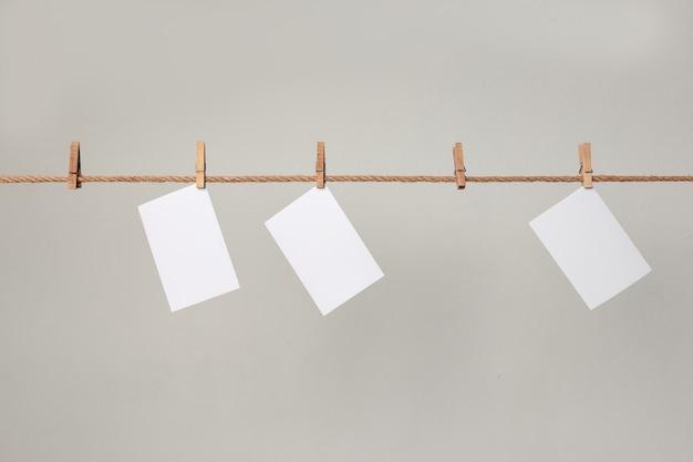 Papel fotográfico blanco. colgando de un tendedero con pinzas para la ropa. Foto Premium