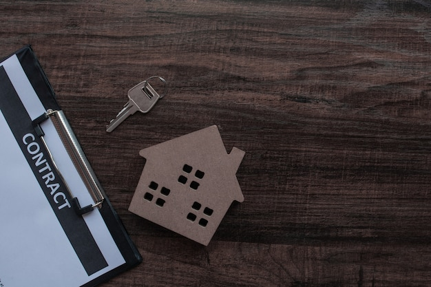 Papel inmobiliario y contrato con llave de la casa en mesa de madera Foto Premium