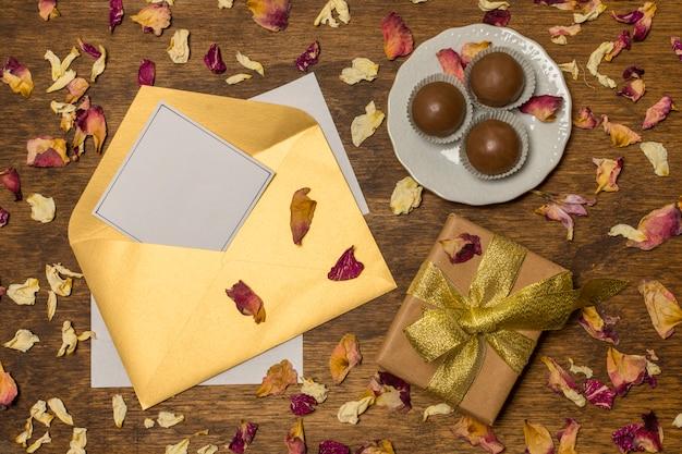 Papel en letra junto a plato con caramelos y caja actual entre hojas secas Foto gratis