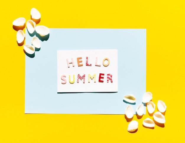 Papel con letras hola verano y conchas marinas. Foto gratis