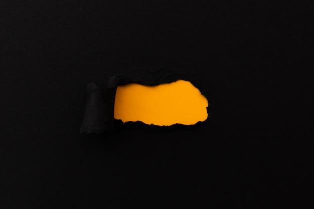 Papel rasgado con espacio en blanco para su mensaje. papel rasgado negro con fondo naranja Foto gratis