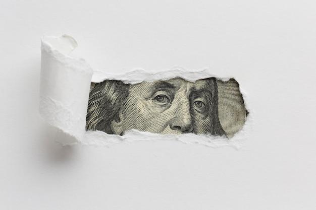Papel rasgado que revela billete de un dólar Foto gratis