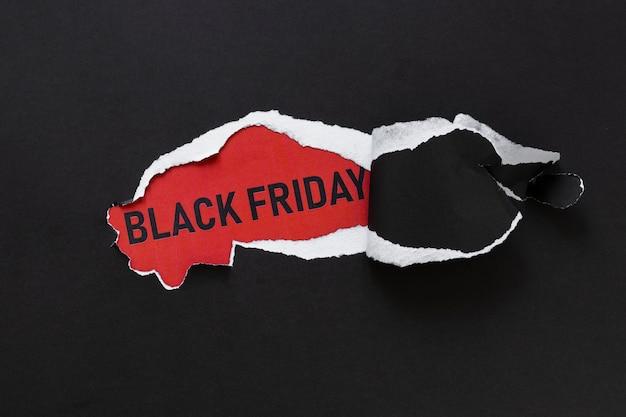Papel rasgado que revela el texto del viernes negro Foto gratis