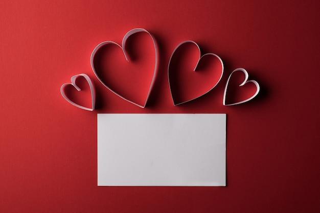 Papel rojo del corazón y en blanco con la tarjeta de nota en fondo rojo Foto gratis